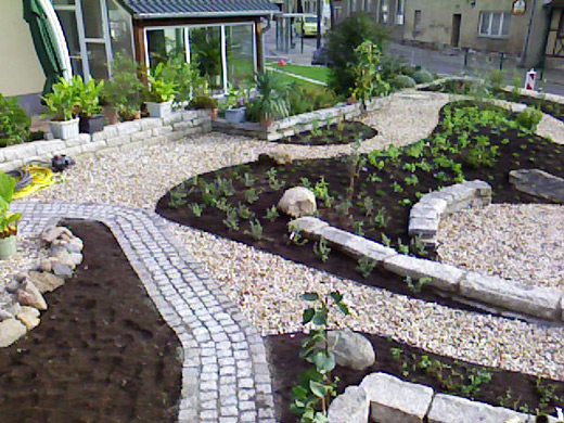 Typisch für den mediterranen Garten sind helle Steinwege und Elemente zwischen den Beeten