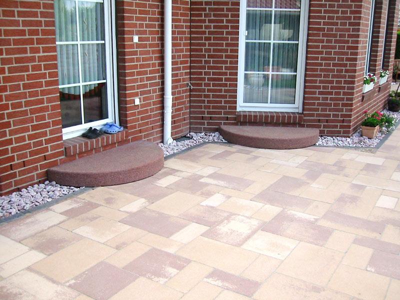 Helle Betonplatten aufgelockert mit Natursteinen von Rollrasen Schirmer